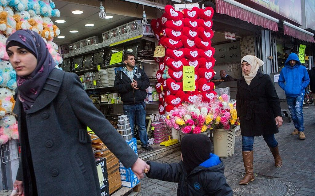 Palestinians walk by a shop selling heart-shaped pillows for Valentine's day, in the center of the West Bank city of Ramallah, on February 14, 2015 (Miriam Alster/FLASH90)