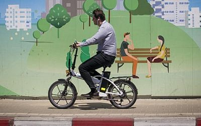 A man rides his electric bike past a mural set up near a construction site in Ramat Gan, near Tel Aviv. April 29, 2015. (Miriam Alster/FLASH90)