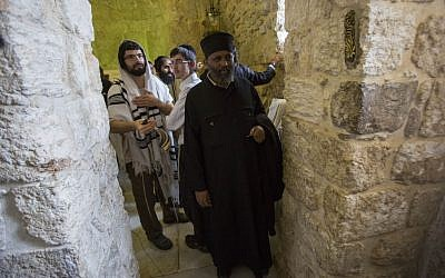 An Ethiopian Christian man poses for a picture alongside Orthodox Jewish worshipers at King David's Tomb, near Zion Gate in Jerusalem's Old City, on May 31, 2015 (Yonatan Sindel/Flash90)