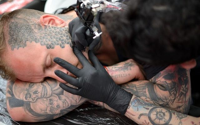 A man gets his face tattooed during the third annual tattoo festival at Haoman Club in Tel-Aviv on June 6, 2015 (Tomer Neuberg/Flash90)