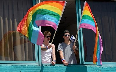 Men wave rainbow flags at the Annual Gay Pride Parade in Tel Aviv, June 12, 2015 (Flash90/Gili Yaari)