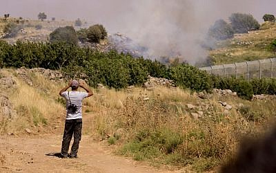 Druze watch the bombing between Syrian forces from the Israeli side of the border with Syria in the Golan Heights, on June 16, 2015. (Basel Awidat/Flash90)