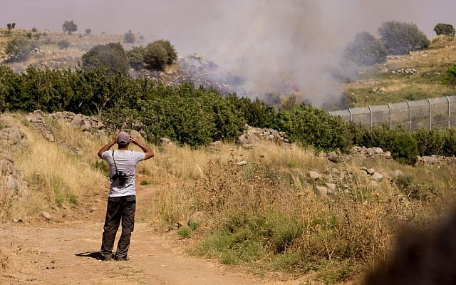 A Druze man watches the bombing between Syrian forces from the Israeli side of the border with Syria in the Golan Heights due, on June 16, 2015. (Basel Awidat/Flash90)