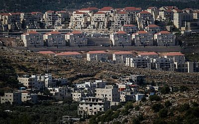 Construction in the ultra-Orthodox settlement of Beitar Illit, with the Arab village of Wadi Fukin in the foreground, on June 17, 2015. (Nati Shohat/Flash90)