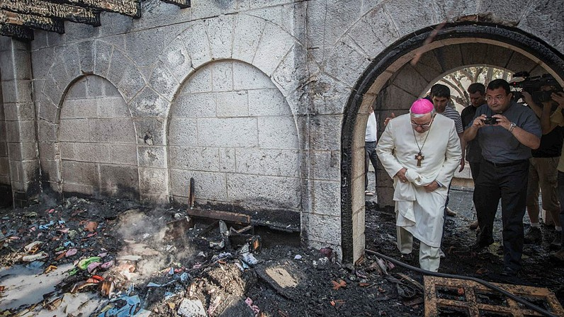 A priest inspects the damage caused to the Church of the Multiplication at Tabgha, on the Sea of Galilee, in northern Israel, which was set on fire in what police suspect was an arson attack, on June 18, 2015. (Basel Awidat/Flash90)