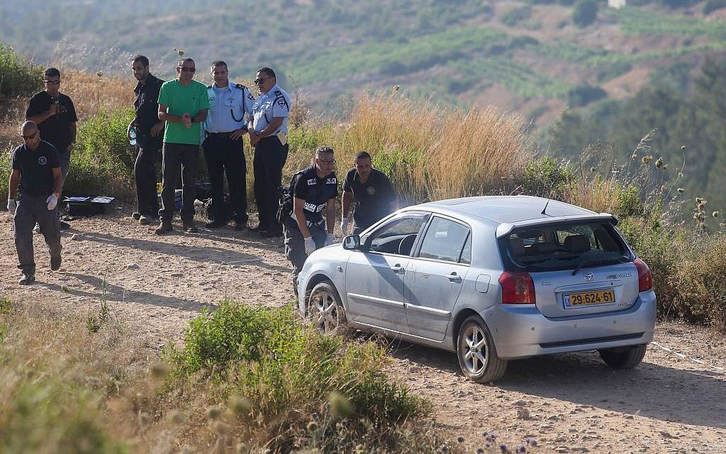 Israeli security officials stand near the car belonging to Israeli victims of an attack by a Palestinian terrorist near the Dolev settlement in the West Bank on June 19, 2015. (Flash90)