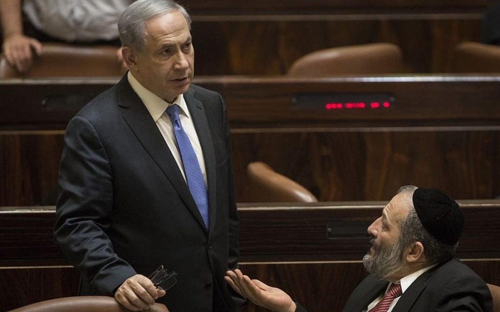 Prime Minister Benjamin Netanyahu speaks with then-economy minister Aryeh Deri in the Knesset, June 29, 2015. (Hadas Parush/Flash90)
