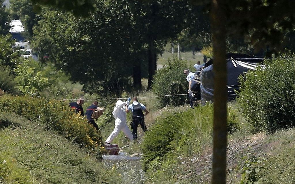 Investigating police officers work outside the plant where a terrorist attack took place, Friday, June 26, 2015 in Saint-Quentin-Fallavier, southeast of Lyon, France. (AP Photo/Laurent Cipriani)