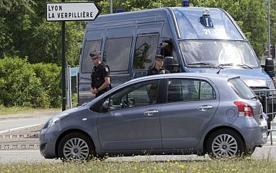 Police officers guard the road leading to a plant in Saint-Quentin-Fallavier, southeast of Lyon, France, Saturday, June 27, 2015, where an attack took place yesterday June 26. (AP/Michel Euler)