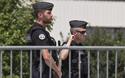 Police officers guard a road leading to a plant which was attacked on Friday in Saint-Quentin-Fallavier, southeast of Lyon, France, Saturday, June 27, 2015. (AP/Michel Euler)
