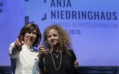 CNN journalist Christiane Amanpour, left, hands the 2015 Anja Niedringhaus Award to photographer Heidi Levine, in Berlin, Thursday, June 25, 2015. (AP Photo/Michael Sohn)