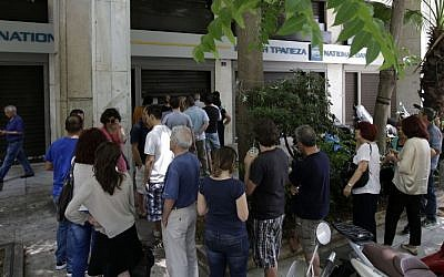 People line up to use ATMs of a bank in central Athens, on June 28, 2015. (AP/Thanassis Stavrakis)