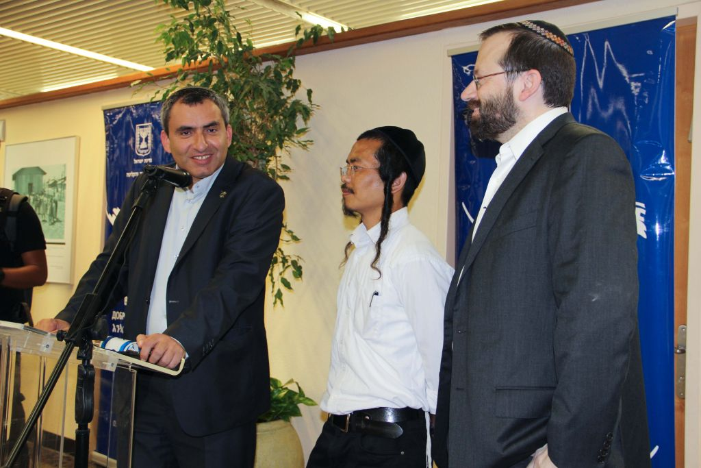 Absorption Minister Ze'ev Elkin (L) speaks to a gathering of new immigrants from India, alongside his translator (C) and Shavei Israel director Rabbi Michael Freund (R) on June 18, 2015. (Laura Ben-David/Shavei Israel)