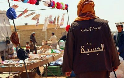 """A member of the Islamic States vice police known as """"Hisba,"""" patrols a market in Raqqa City, Syria, in this verified photo released by a militant website on April 17, 2015. The Arabic words on the vest read, """"The Islamic State - Hisba (vice police)."""" (Militant website via AP)"""