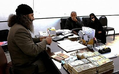 Two Syrian citizens, right, sit in the office of an inheritance judge of Islamic State, in the town of al-Tabqa in Raqqa City, Syria, in this verified photo released on Feb. 10, 2015 by a militant website. (Militant website via AP)