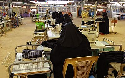 Women in niqabs - enveloping black robes and veils that leaves only the eyes visible - sew more niqabs, which are required for women in Islamic State-held territory, in a factory in Mosul, Iraq, in this verified photo released on Jan. 31, 2014 by a militant website. (Militant website via AP)