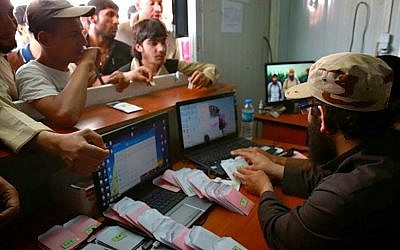 People stand at the window of a media distribution point to receive CDs from an Islamic State militant, right, in Mosul, Iraq in this verified photo released on May 4, 2015 by a militant website. (Militant website via AP)
