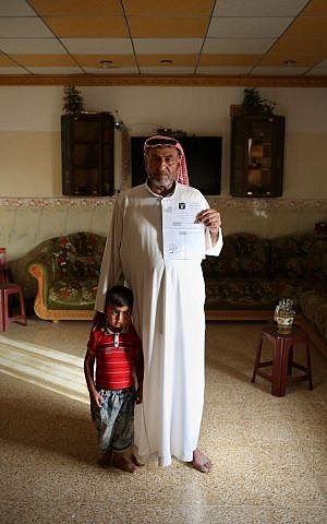 Sheikh Abdullah Ibrahim poses with his son while holding an Islamic State-issued death certificate - all that he has left of his wife, Buthaina Ibrahim, an outspoken human rights activist and official, in the village of Eski Mosul, northern Iraq on May 17,2015. (Bram Janssen/AP)