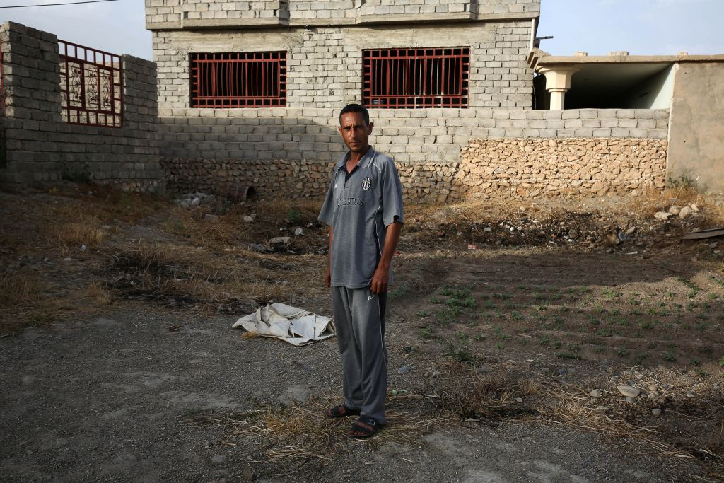 Bilal Abdullah poses for a portrait in the village of Eski Mosul in northern Iraq on May 26, 2015, nearly a year after Islamic State militants took over the village. (Bram Janssen/AP)