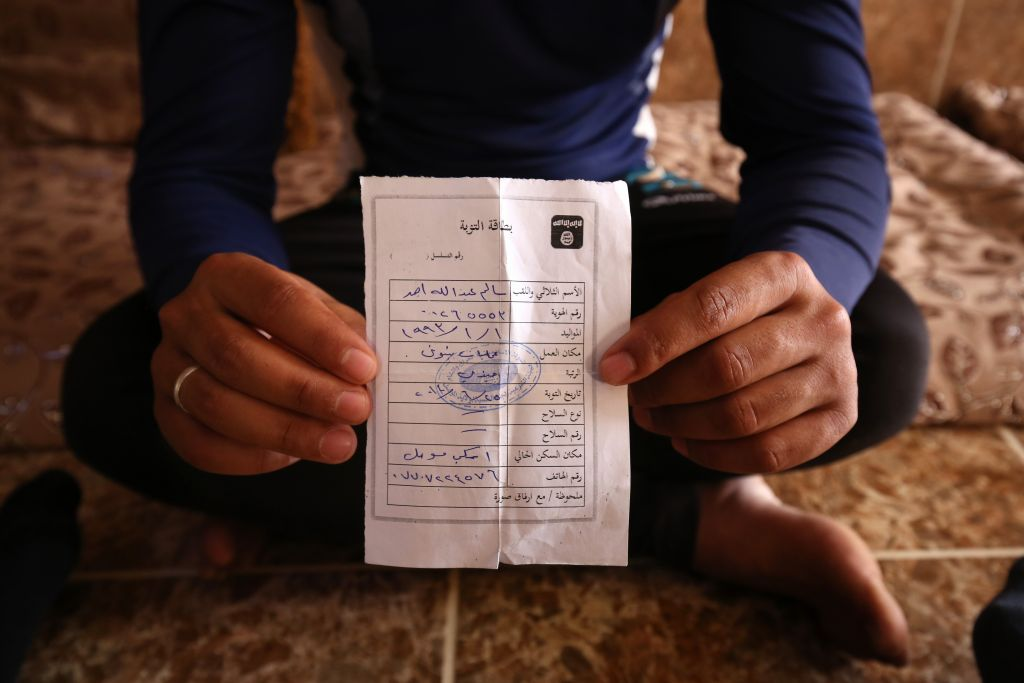 """Salim Ahmed, a former Iraqi Army member, holds his """"repentance card"""" on May 27, 2015. He received the card from the Islamic State shortly after the militants took over his home village of Eski Mosul in northern Iraq. (Bram Janssen/AP)"""