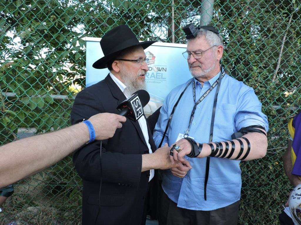 A rabbi places tefillin on Ron Mix, a Jewish Hall of Fame offensive tackle mostly for the San Diego Chargers during a visit to Israel on June 21, 2015. (Ben Sales/JTA)