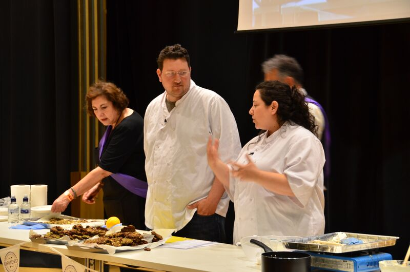 Husband-and-wife couple Itamar Srulovich (center) and Sarit Packer (right) demonstrate a cooking technique at London's Gefiltefest on June 28, 2015. The couple runs a wildly successful bistro in the city center, Honey & Co. (courtesy)
