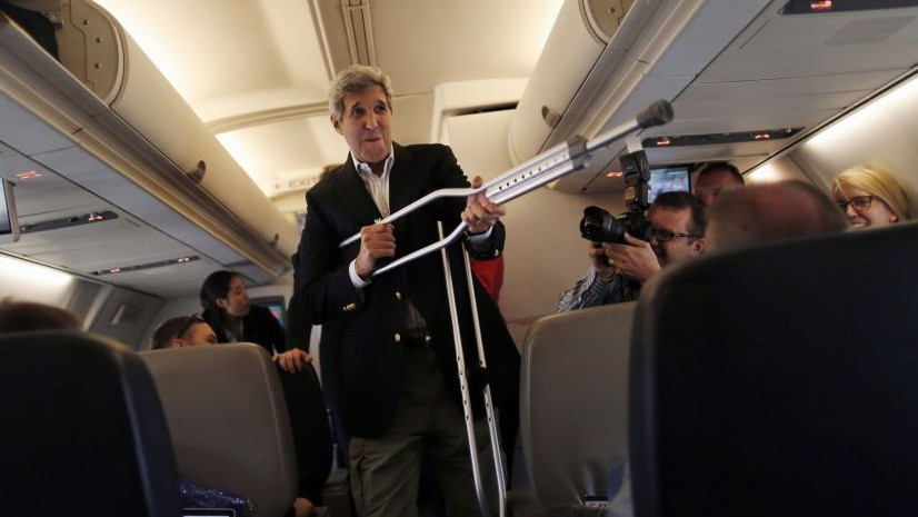Secretary of State John Kerry plays with his crutches as he talks to reporters before leaving from Andrews Air Force Base, Md., Friday, June 26, 2015, en route to Vienna, Austria, for talks on the Iranian nuclear deal. (Carlos Barria/Pool Photo via AP)