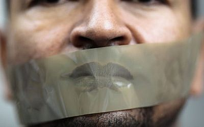 A man with tape on his mouth attends a demonstration in front of a court to support Ahmed Mansour, a senior journalist with the Qatar-based broadcaster Al-Jazeera, June 22, 2015. (AP/Markus Schreiber, File)