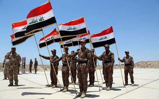 Sunni tribal volunteers with national flags stand in formation during their graduation ceremony in Habaniyah, 80 kilometers (50 miles) west of Baghdad, Iraq, Wednesday, June 17, 2015 (AP Photo/ Khalid Mohammed)