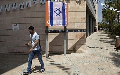 An Israeli man walks past the Orange company logo covered with an Israeli flag at the Partner Orange offices in the city of Rosh Ha'ayin, Israel. Thursday, June 4, 2015. (AP Photo/Dan Balilty)