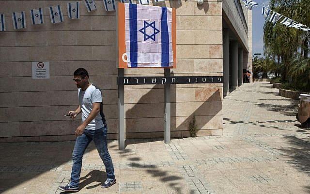 An Israeli man walks past the Orange company logo covered with an Israeli flag at the Partner Orange offices in the city of Rosh Ha'ayin, Israel. Thursday, June 4, 2015. (AP Photo/Dan Balilty)