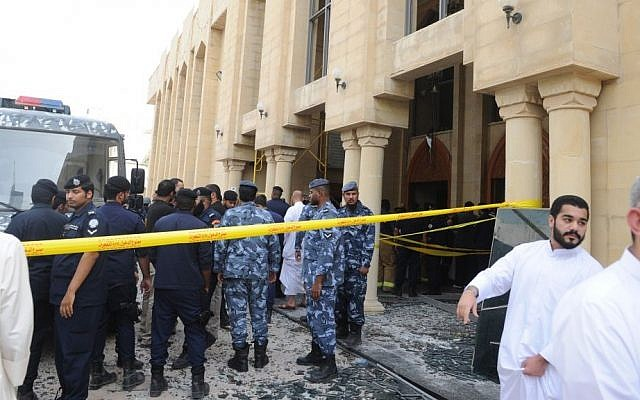 Security forces and officials gather at a Shi'ite mosque after a deadly blast claimed by the Islamic State group that struck worshipers attending Friday prayers in Kuwait City, Friday, June 26, 2015. (AP Photo)