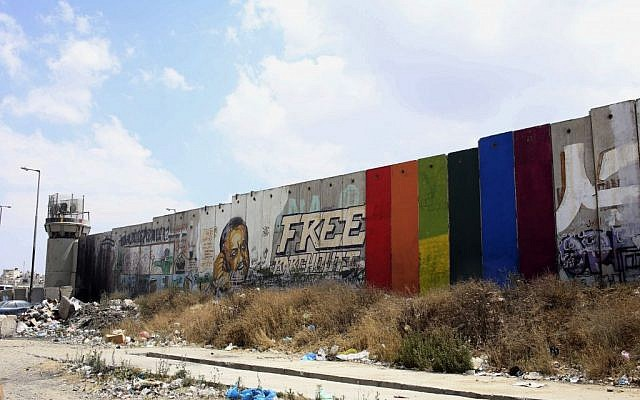 This Monday, June 29, 2015 photo provided by Palestinian artist Khaled Jarrar shows his painting of a rainbow flag on six slabs of the West Bank security barrier in the West Bank city of Ramallah. (Khaled Jarrar via AP)