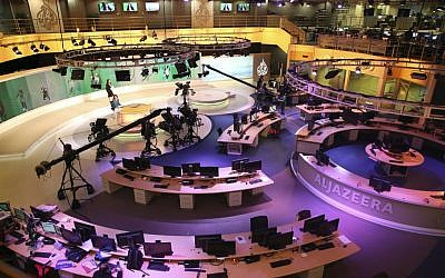 In this Jan. 1, 2015, file photo, staff members of Al-Jazeera International work at the news studio in Doha, Qatar. Ahmed Mansour, a prominent Al-Jazeera Arabic journalist, was detained Saturday, June 20, in Germany over an Egyptian arrest warrant, the Qatar-based broadcaster reported. (AP/Osama Faisal)
