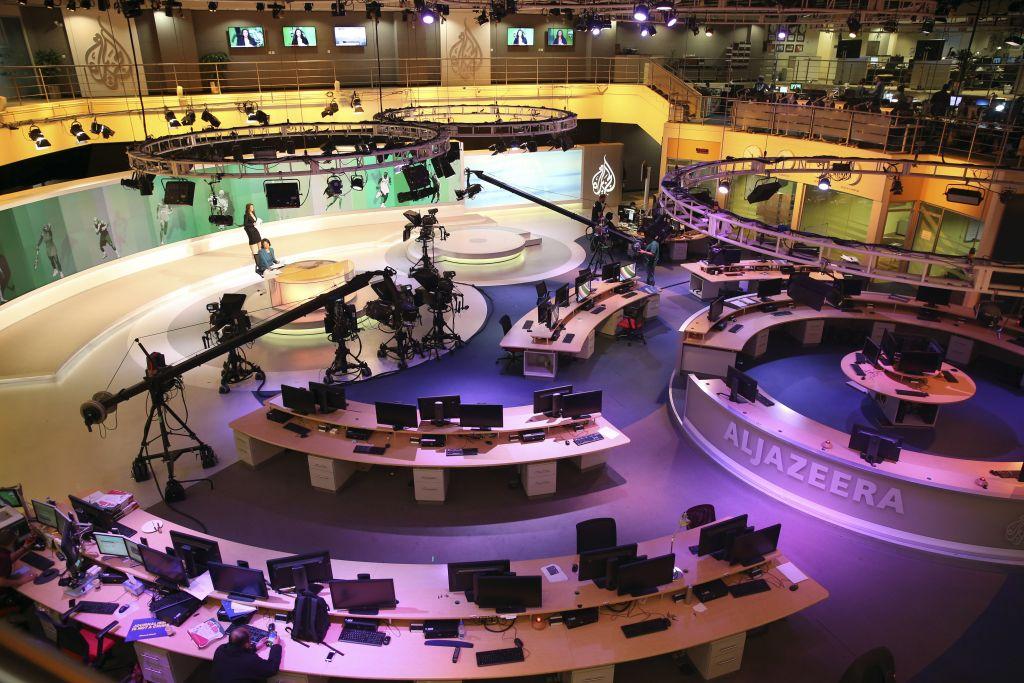 In this Jan. 1, 2015, file photo, staff members of Al-Jazeera International work at the news studio in Doha, Qatar. (AP/Osama Faisal)