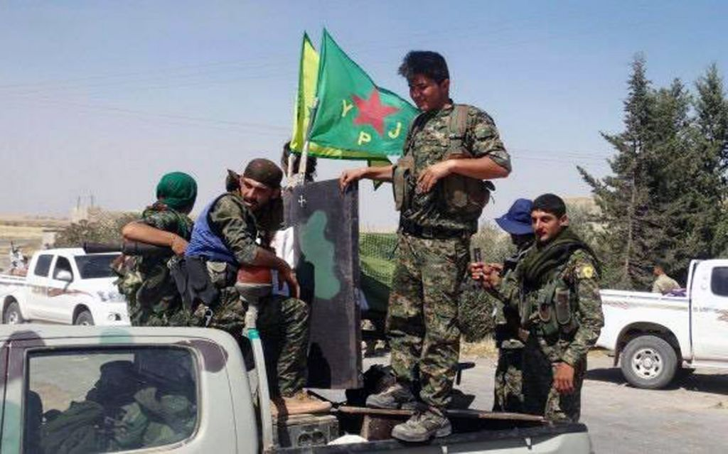 Kurdish fighters of the YPG sit on their pickup truck in the town of Ein Eissa, north of Raqqa city, Syria, Tuesday, June 23, 2015. (The Kurdish fighters of the People's Protection Units via AP)