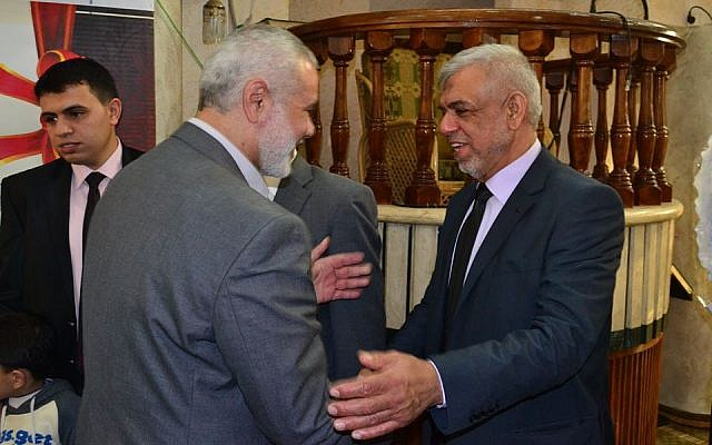 Gaza-based journalist Mustafa Sawwaf shakes hands with former Hamas prime minister Ismail Haniyeh in March 2015 (Mustafa Sawwaf Facebook page)