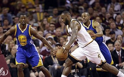 Cleveland Cavaliers forward LeBron James (23) drives on Golden State Warriors forward Harrison Barnes (40) and guard Andre Iguodala (9) during the first half of Game 6 of basketball's NBA Finals in Cleveland, Tuesday, June 16, 2015. (AP/Tony Dejak)