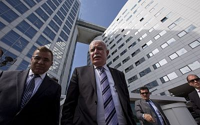 Palestinian Authority Foreign Minister Riyad al-Maliki, center, waits on the steps of the International Criminal Court after answering questions of reporters in The Hague, Netherlands, Thursday, June 25, 2015. (AP Photo/Peter Dejong)