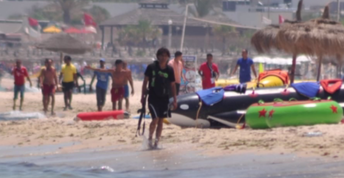 Seifedinne Rezgui, the gunman who allegedly murdered dozens in Tunisia on June 26, 2015, is shown walking with his weapon on the beach after the massacre in this still from Sky News footage. He was later shot in a side street, Sky reported. (Sky News screenshot)