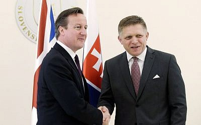 Slovakia's Prime Minister Robert Fico, right, welcomes British Prime Minister David Cameron, left, in Bratislava, Slovakia, Friday, June 19, 2015. (AP/Petr David Josek)