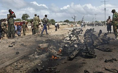 Somali soldiers stand near the wreckage at the scene of a suicide car bomb attack which targeted a convoy of foreign officials, in Mogadishu, Somalia on Wednesday, June 24, 2015. (AP Photo)