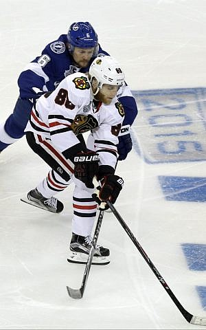 Tampa Bay Lightning defenseman Anton Stralman, back, battles Chicago Blackhawks right wing Patrick Kane for the puck with during the first period in Game 2 of the NHL hockey Stanley Cup Final on Saturday, June 6, 2015, in Tampa Fla. (AP Photo/John Raoux)