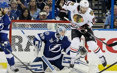 Tampa Bay Lightning goalie Andrei Vasilevskiy (88) makes a save in the third period of Game 2 of the Stanley Cup Finals against the Chicago Blackhawks at Amalie Arena in Tampa, Fla., Saturday, June 6, 2015. The Blackhawks player jumping at right is Antoine Vermette. Tampa defeated Chicago 4-3. (Dirk Shadd/The Tampa Bay Times via AP)