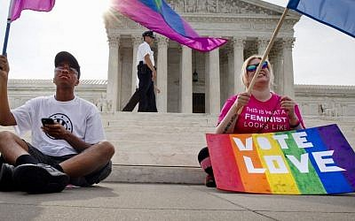 Carlos McKnight, 17, of Washington, left, and Katherine Nicole Struck, 25, of Frederick, Md., hold flags in support of gay marriage as security walks behind outside of the Supreme Court in Washington DC, Friday, June 26, 2015. (AP/Jacquelyn Martin)