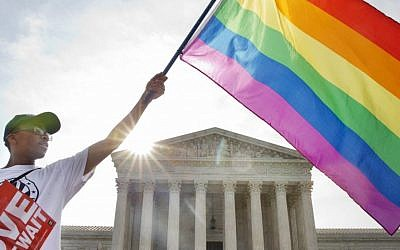 Carlos McKnight of Washington, waves a flag in support of gay marriage outside of the Supreme Court in Washington, Friday June 26, 2015. (AP/Jacquelyn Martin)