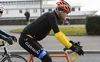 US Secretary of State John Kerry rides a bike after a bilateral meeting with the Iranian Foreign Minister in Lausanne, Switzerland, on March 16, 2015.  (Jean-Christophe Bott/Keystone via AP)