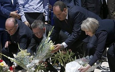 From right to left: British Home Secretary Theresa May, Tunisian Interior Minister Mohamed Najem Gharsalli, , German Interior Minister Thomas de Maiziere and French Interior Minister Bernard Cazeneuve lay flowers on the beach in front of the Imperial Marhaba hotel in the Mediterranean resort of Sousse, Tunisa, Monday, June 29, 2015 (Abdeljalil Bounhar/AP)