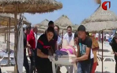 In this screen grab taken from video provided by Tunisia TV1, injured people are treated on a Tunisian beach Friday June 26, 2015. Two gunmen rushed from the beach into a hotel in the Tunisian resort town of Sousse Friday, killing at least 37 people and wounding six others in the latest attack on the North African country's key tourism industry, the Interior Ministry said. (Tunisia TV1 via AP)