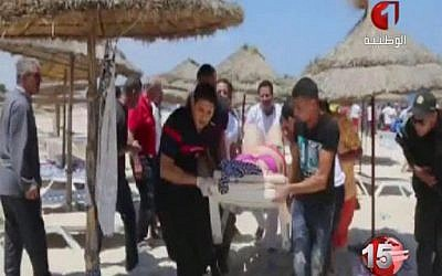 Injured people are treated on a Tunisian beach Friday, June 26, 2015 after a terror attack in which more than 30 people were killed. (Tunisia TV1 via AP)